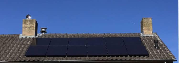 dak met zonnepanelen en blauwe lucht