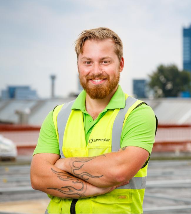trotse zonneplan monteur op grootste zonnepanelen dak van nederland